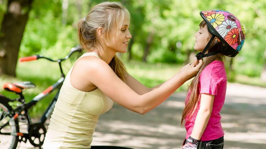 mom fastening helmet on daughter