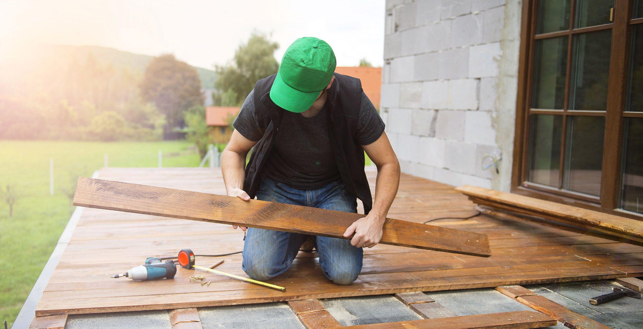 man installing new floor board on patio