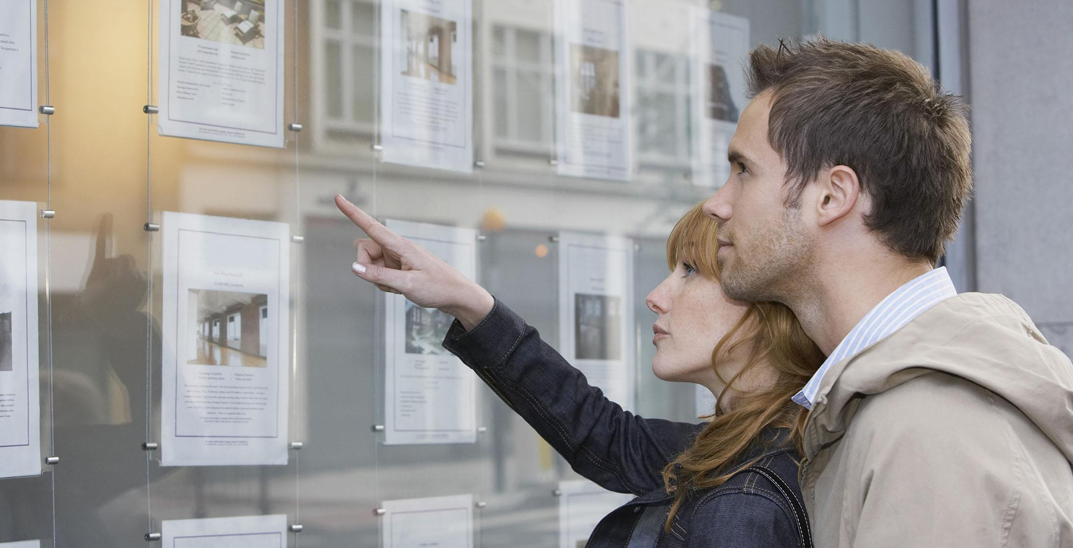 woman pointing out a picture pinned to bulletin board