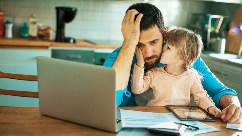 daughter kissing father on the cheek while father looks upset at his documents and laptop