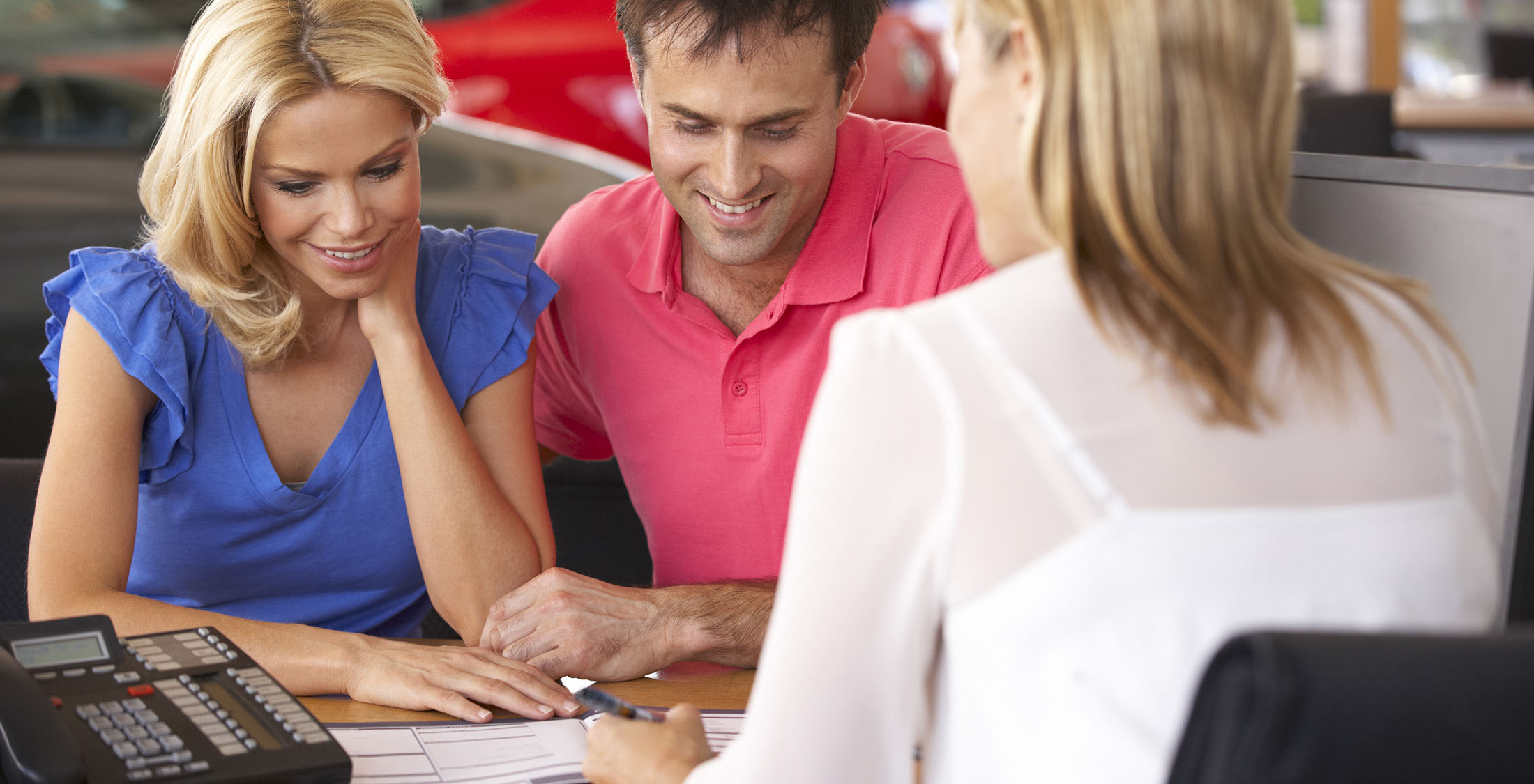 couple looking over documents at car dealership