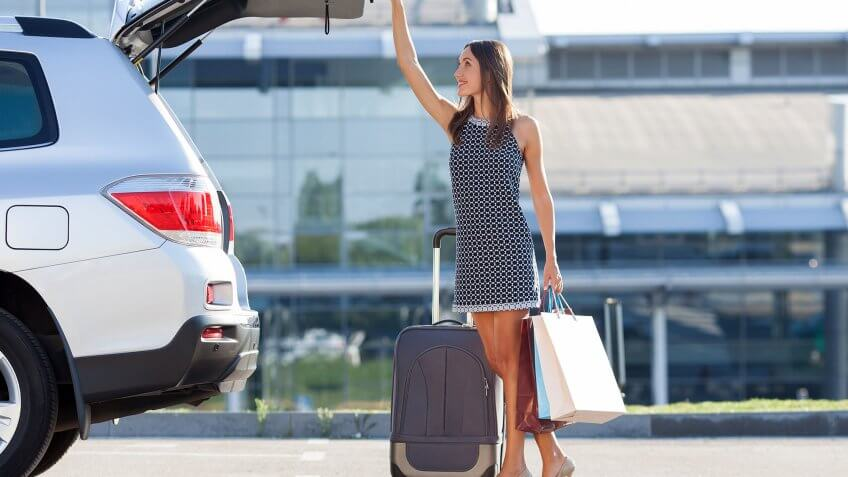 woman closing trunk to suv with luggage by her side