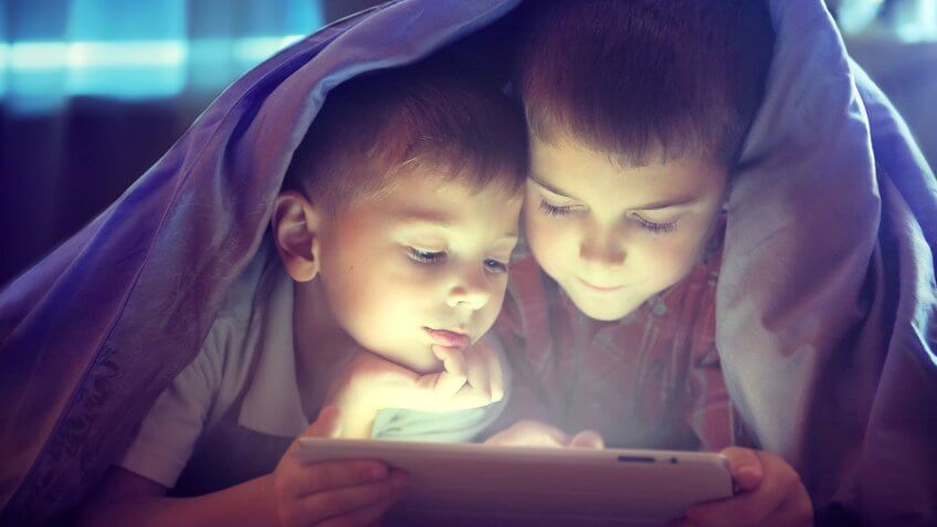 brothers looking at tablet under blanket