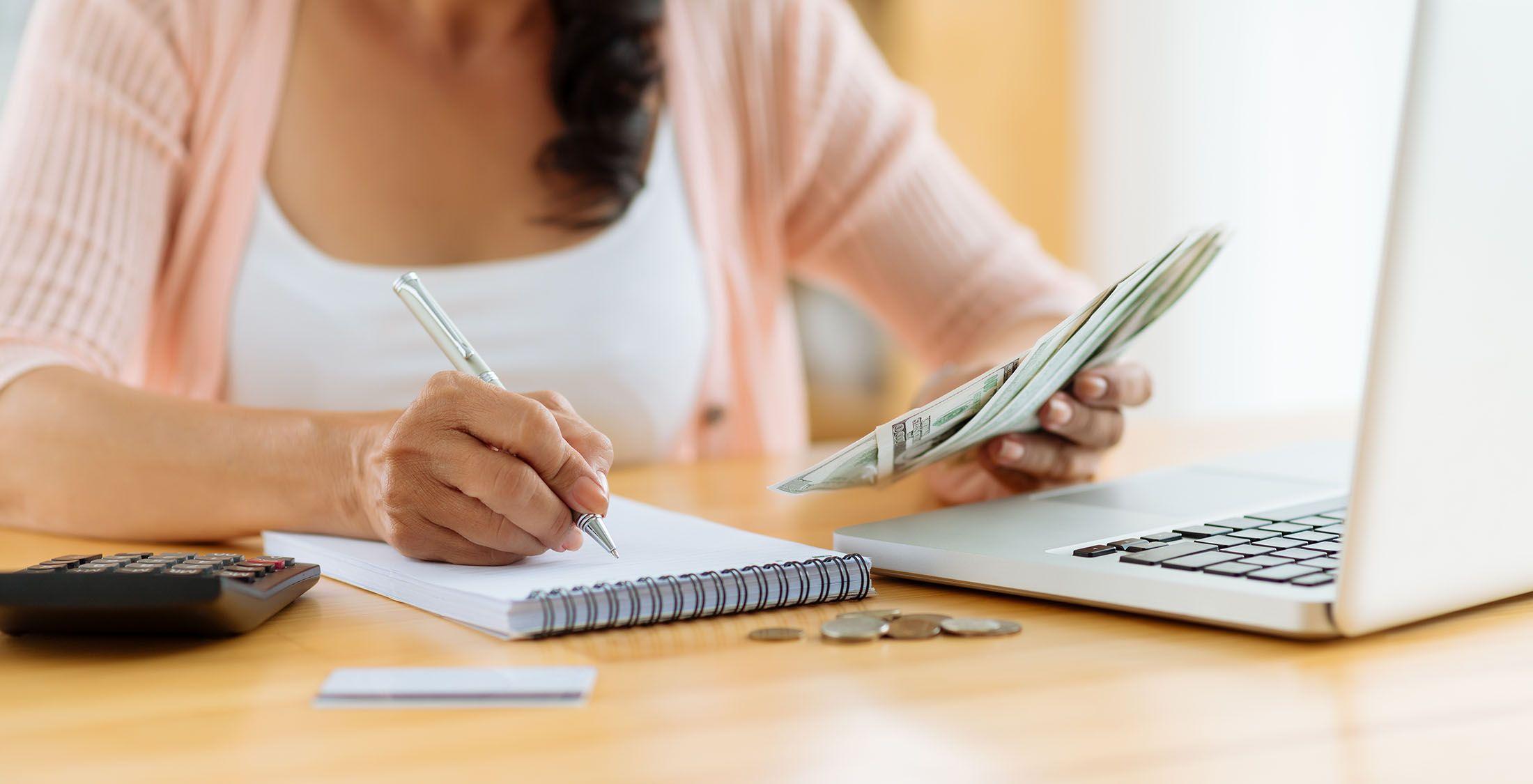 woman with dollar bills budgeting