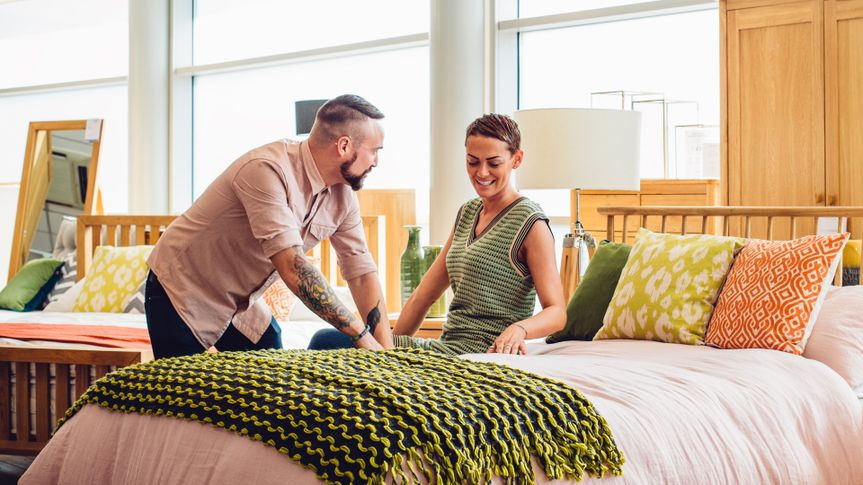 A middle aged couple are shopping in a furniture store for a new bedroom, the customers are both sat on the bed to see how comfortable it is, trying it out.