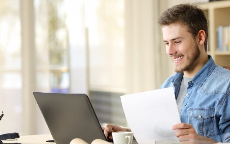man smiling at laptop and paper