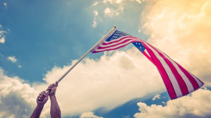 American flag with stars and stripes hold with hands against blue sky.