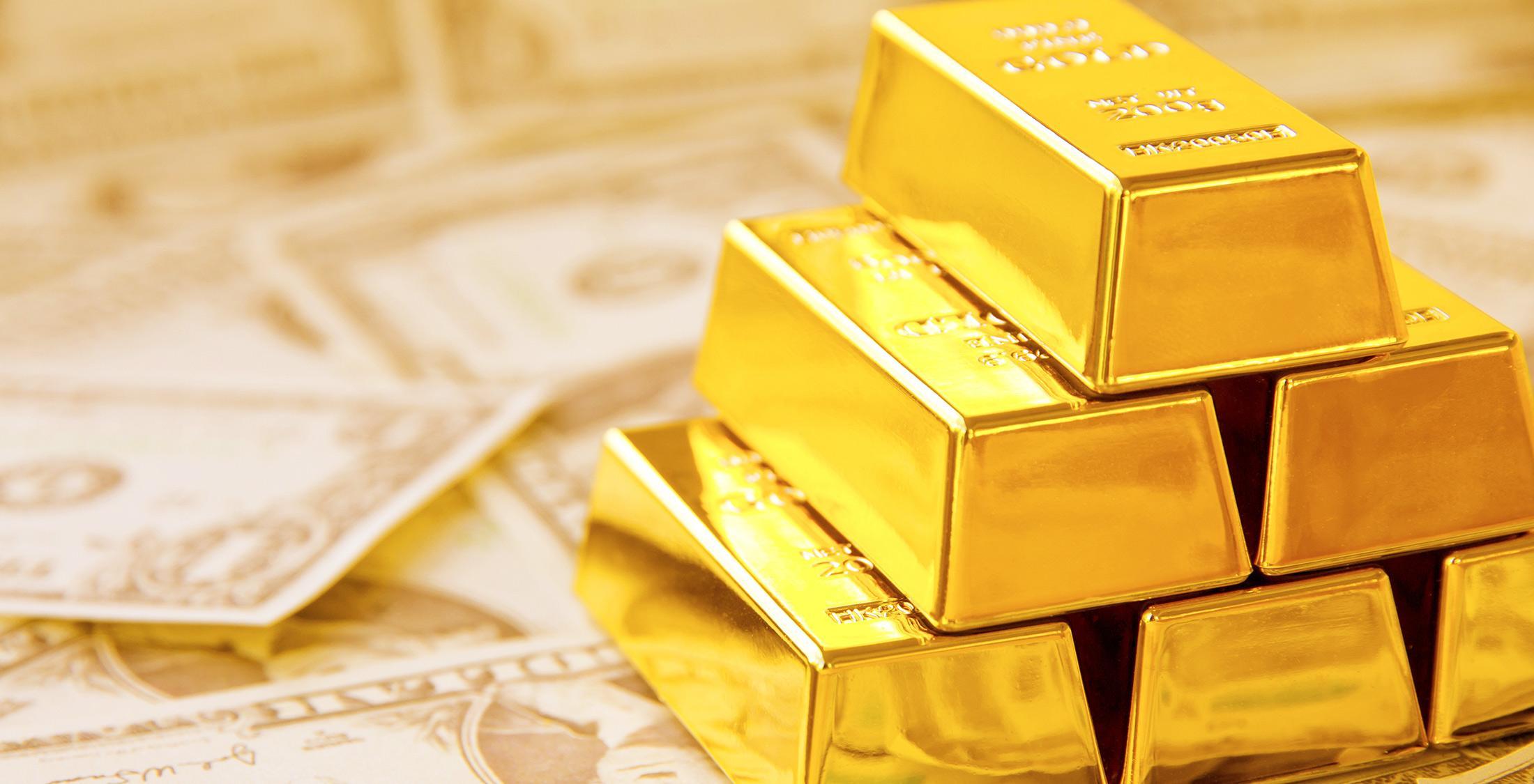 gold bars atop dollar bills