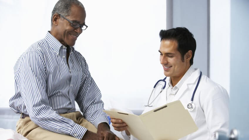 Doctor In Surgery With Male Patient Reading Notes.