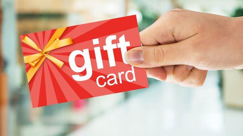 Cropped image of person's hand holding gift card.