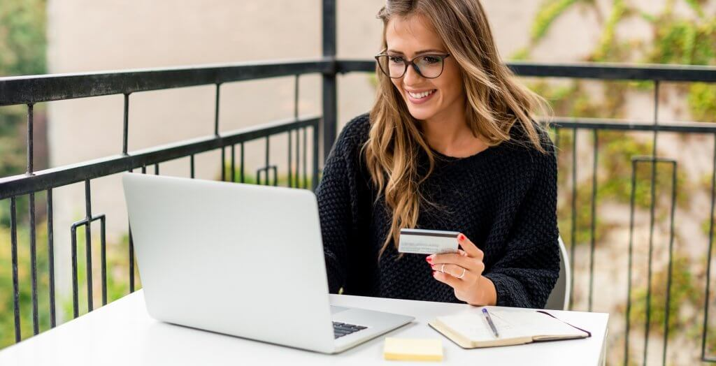 woman smiling and using laptop to input credit card info