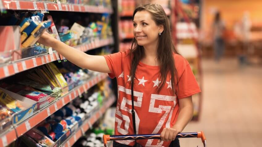 Young woman shopping for cereal, bulk in a grocery supermarket.