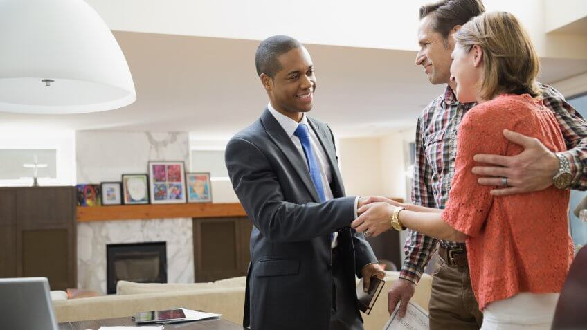 Couple shaking hands with financial advisor.