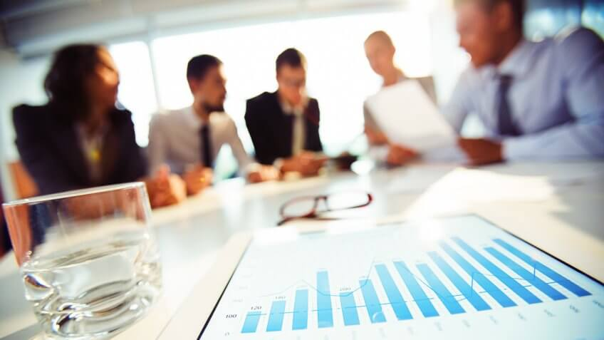 coworkers in meeting with focus on chart