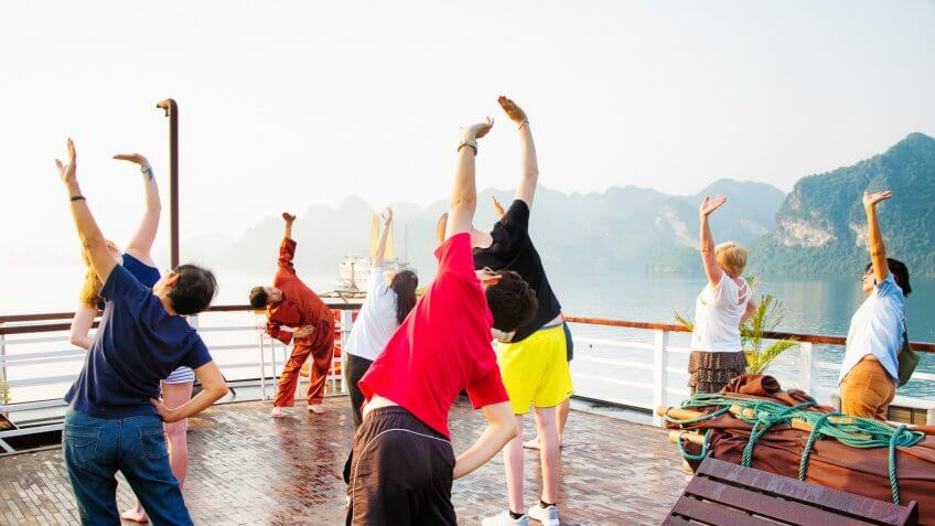 Halong Bay, Vietnam - April 15, 2015: Tourists exercising while on Halong Bay cruise in Vietnam, mimicking the moves of their teacher.