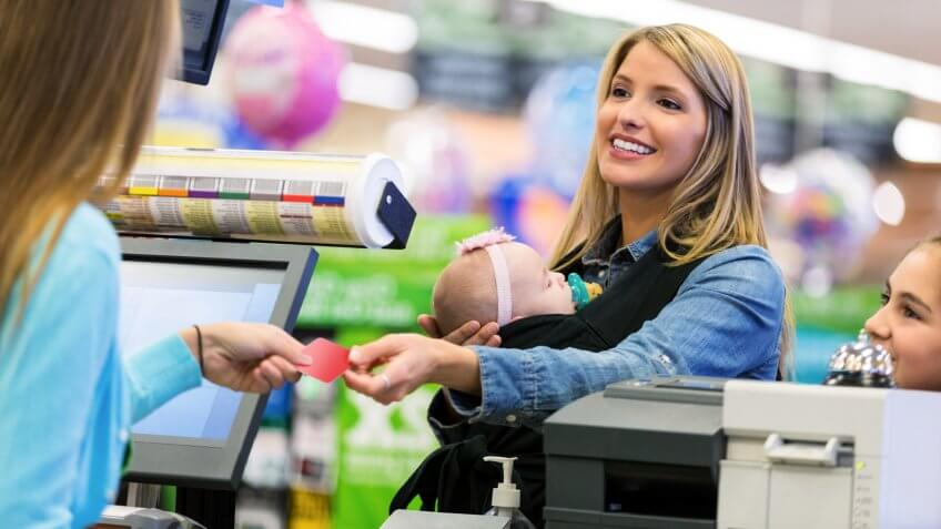 Mid adult Caucasian woman is shopping local grocery store or supermarket with elementary age daughter and infant.