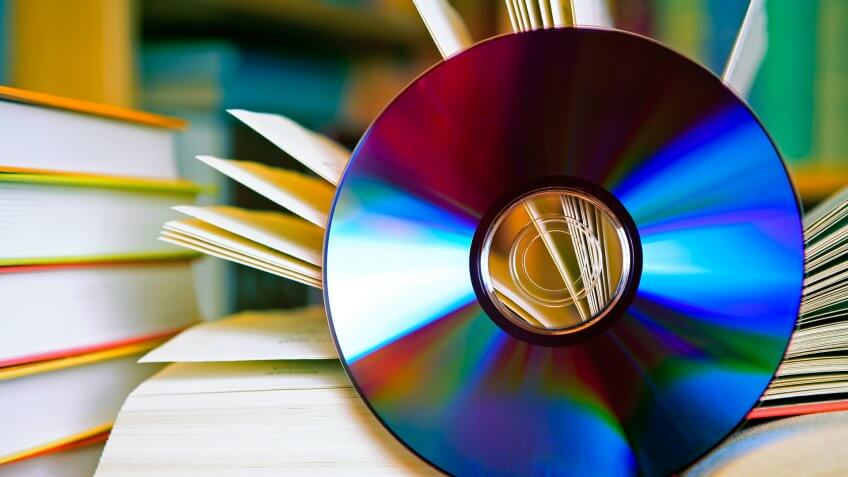 A DSLR photo of an open book with a CD in front of it.