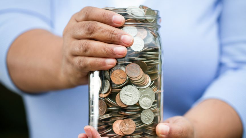 Woman holding a jar of money.
