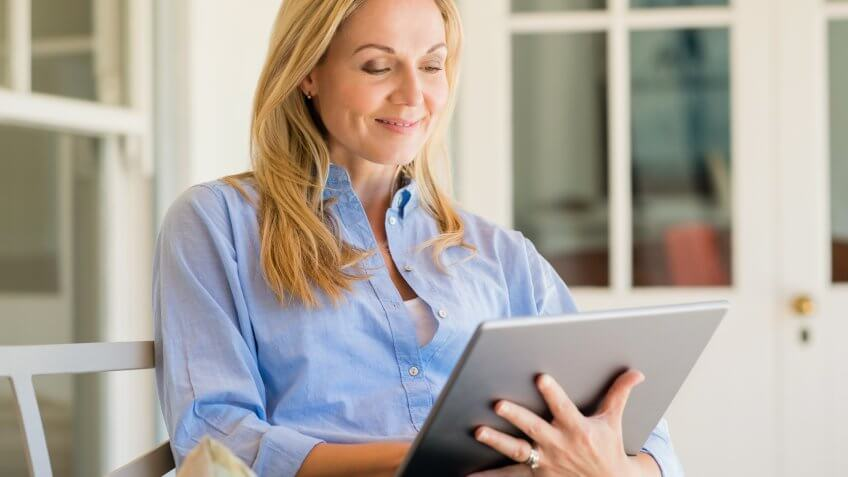 Portrait of a business woman using digital tablet in open air porch.
