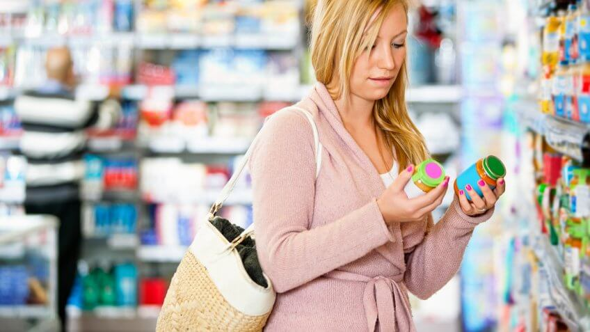Young woman holding jar in the supermarket with people in the background.