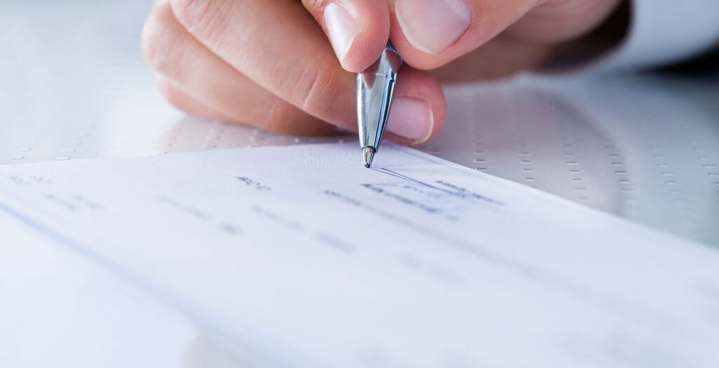 person signing some type of document or check
