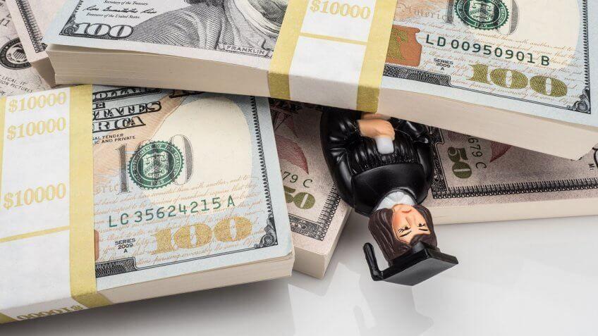 graduate figurine buried under stacks of cash