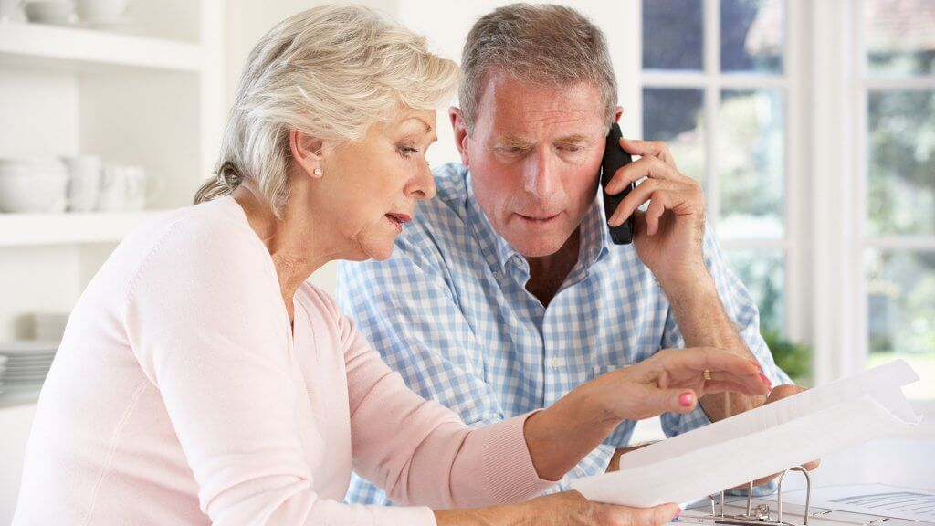 retired couple looking at paperwork and calling someone