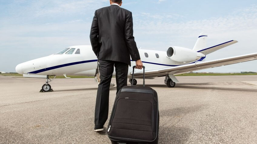 man with luggage walking toward a private jet