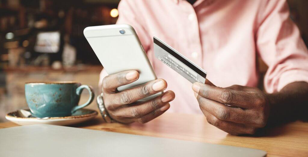 person holding credit card and phone with coffee