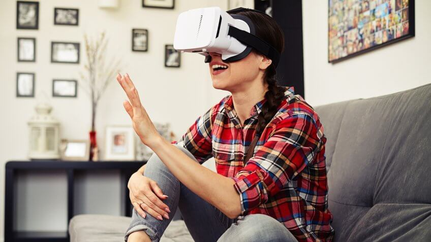 Woman wearing 8i VR goggles on a couch with her hand in the air