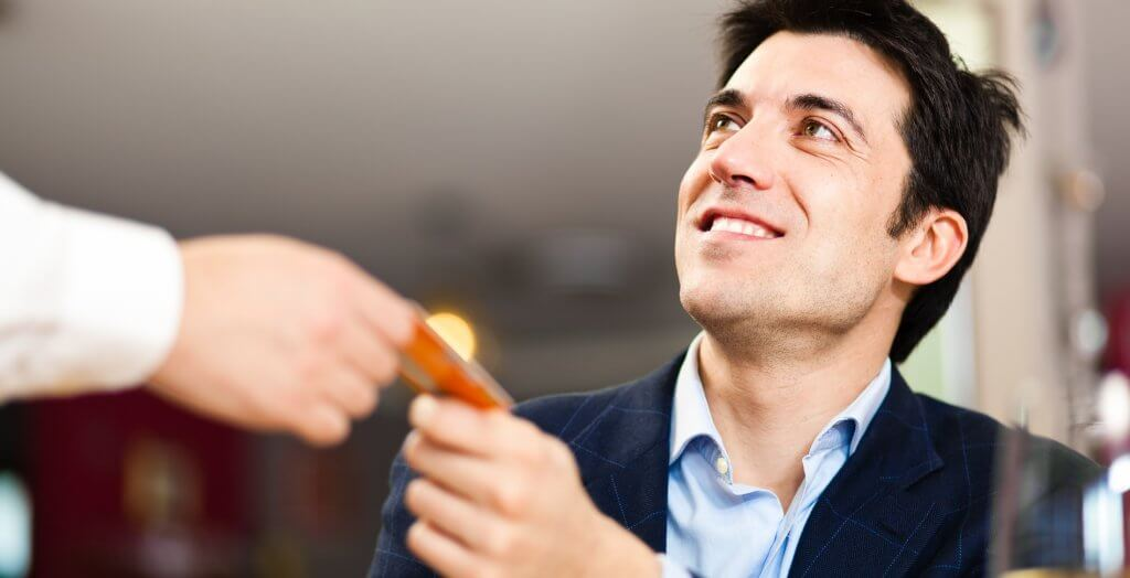 man handing credit card to waiter