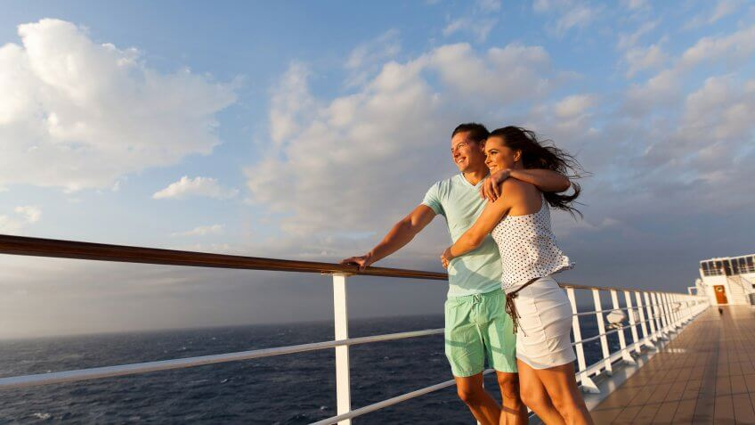 loving married couple standing on cruise deck enjoying sunset together.
