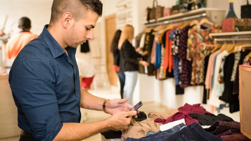 man on phone inside clothing store