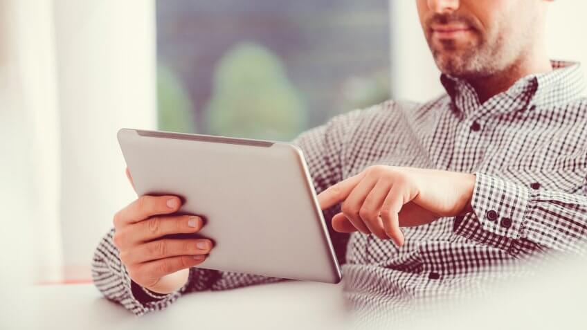 Handsome man wearing glasses and shirt using a digital tablet at home.