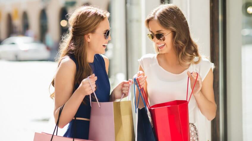 sale, consumerism and people concept - happy young women with shopping bags talking at shop window in city.
