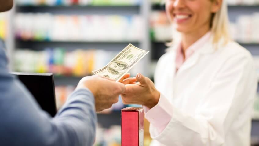Unrecognizable customer paying with cash in pharmacy.