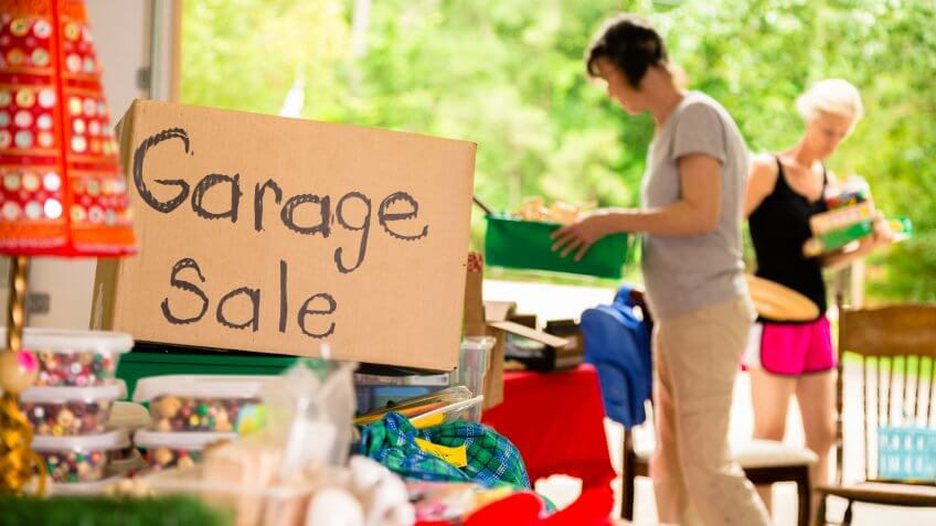Consumerism:  Adult women shopping at a garage sale in suburbs.