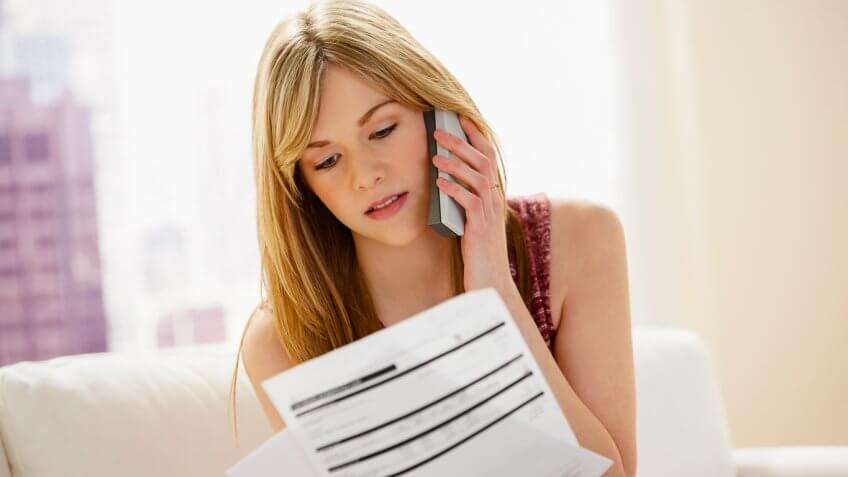 woman on phone looking at financial statements