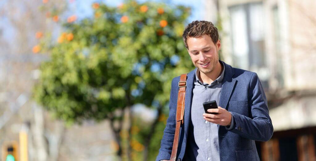 man walking looking at phone tree in background