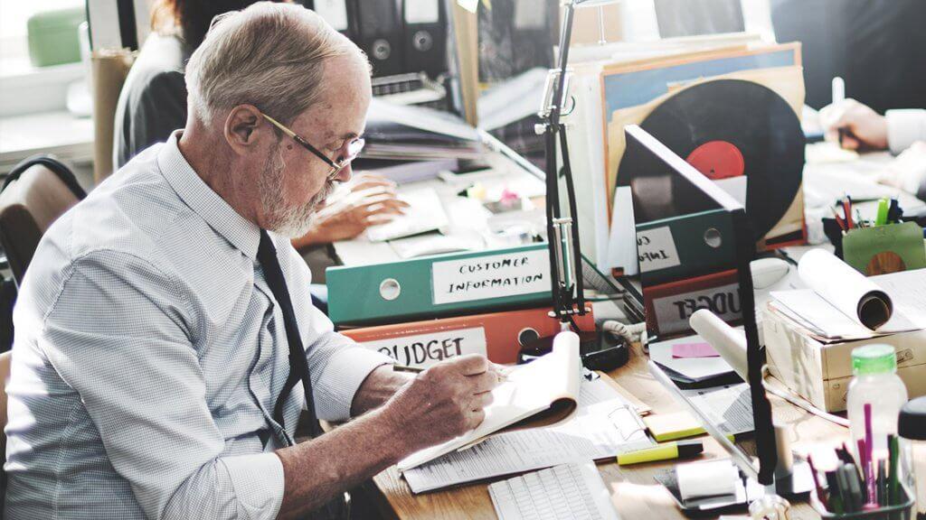 older man at desk reviewing budget information