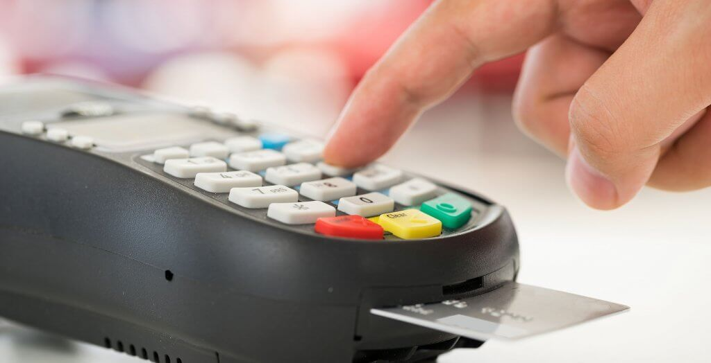 person inserting chip card into machine and entering PIN number