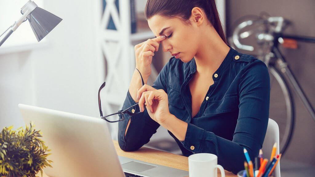 woman taking off glasses frustrated at work
