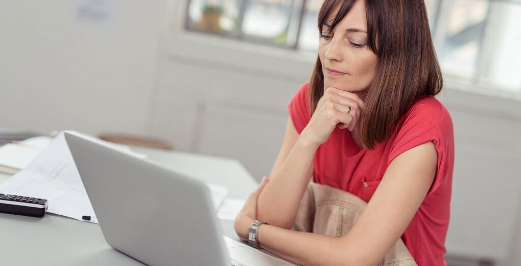 woman thinking about something in front of her laptop