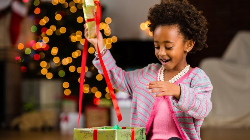 African American preschool girl opening Christmas present.