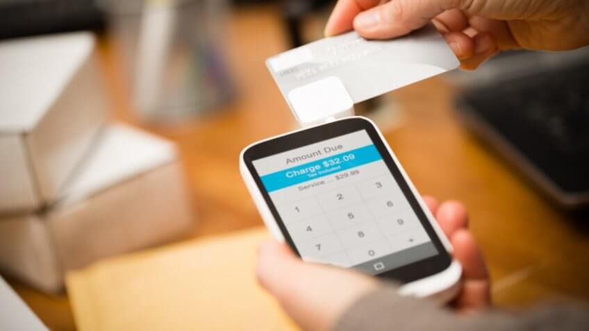 person swiping card on phone card reader