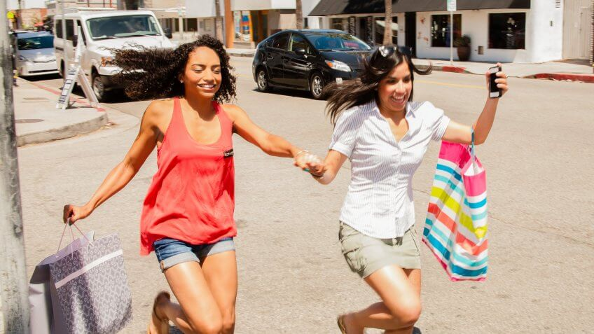Shopping and Consumerism: Excited friends shop together.