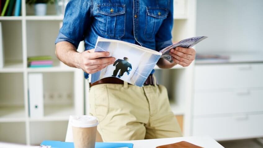 Designer reading a magazine in office.
