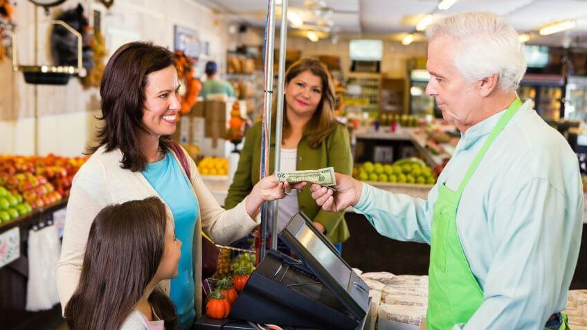 woman handing cash to older cashier