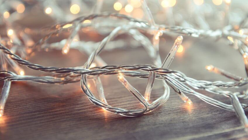 Christmas lights on wooden background.