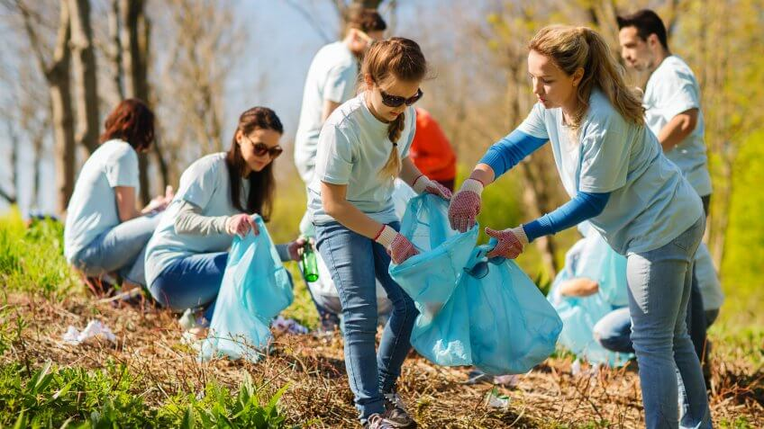 volunteering, charity, cleaning, people and ecology concept - group of happy volunteers with garbage bags cleaning area in park.